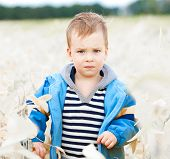 little boy plays in field