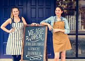 Cheerful business owners standing with open blackboard poster