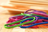 Brightly colored rubber bands with stack of manilla folders in soft focus in background.  Macro with
