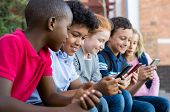 Pupils using mobile phone at the elementary school during recreation time. Group of multiethnic chil poster