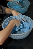 Hands Mixing Blue Coloured Paper Mache In A Mixing Bowl.