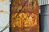 stock photo of chicken-wire  - Old rusty drums behind a chicken wire fence - JPG