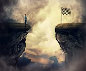 Business Problem As A Young Man Stand On A Cliff Need To Go The Other Side To Reach The Finish Flag. poster