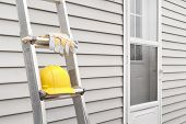 Yellow Hard Hat And Work Gloves On Ladder With House Siding Background. poster