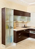 Part Of Modern Kitchen Interior With Cupboard In Warm Tones