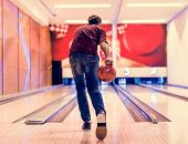 Boy about to roll a bowling ball hobby and leisure concept poster