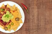 An Overhead Closeup Photo Of Nachos With Cheese, Chilli Con Carne And Guacamole, Traditional Mexican poster