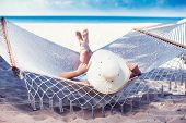 Woman Relaxing On Hammock With White Hat Sunbathing On Vacation poster