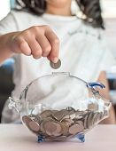 Money Saving Banking Concept With Girl Kid Holding Coin Inserting In Glass Piggy Bank For Educationa poster