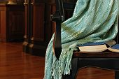 Classic still life of dark wood armchair with old book and handmade afghan in elegantly furnished living room. Conceptual image for solitude and relaxation.  Closeup with shallow dof.