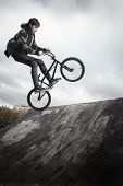 Young man jumping and riding on a BMX bicycle on a ramp over cloudy sky background