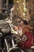 Couple In Love Sit In Shadow Of Trees On Hot Summer Day Near Parked Motorbike, Defocused. Refreshmen poster