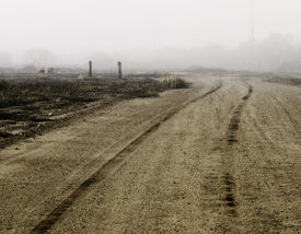 stock photo of dirt road  - Tire tracks in dirt heading of into the distance on a foggy day - JPG