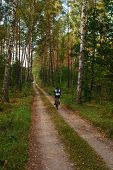 Man biking in a green forest in autumn