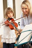 Young girl playing violin in music lesson
