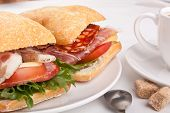 Ciabatta bread sandwich stuffed meat,cheese and vegetables with cup of coffee