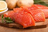 three fresh salmon pieces with lemons on a chopping board