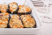 stuffed with cheese aubergines in a dish with wine glasses