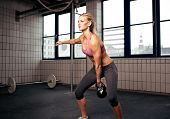 foto of kettles  - Young adult fitness woman doing swing exercise with a kettlebell as a part of a workout - JPG