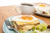 Two Servings of Croque Madame (Ham, Cheese, Bechamel Sauce and Egg Toasted Sandwich) garnished with