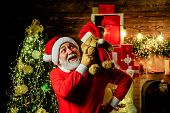 Happy New Year. Santa Man With Toy Teddy. Santa Claus Holds Plush Toy. Happy Santa Claus Hugs Teddy  poster