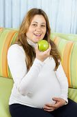 Happy Pregnant Woman Eating A Green Apple