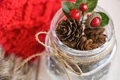 Christmas Pine Cone Or Conifer Cone And Christmas Red Holly Balls In Glass Bottle With Rustic Ribbon poster