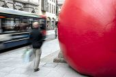 Passersby and a bus go passed Kurt Perschke's giant Red Ball