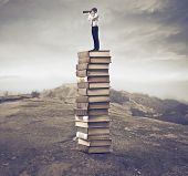 Young businessman standing on a stack of books and using a telescope
