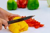 Red And Yellow Pepper Sliced In Thin Slices On A White Background. poster