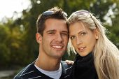 Portrait of attractive young couple in park, smiling.