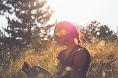 Woman Reading Book In Sunset. Lifestyle Concept. Hipster Woman Relaxing In Sunset In Meadow. Healthy poster