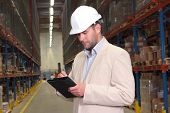 Engineer Making Notes In Warehouse