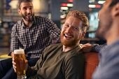 Group of laughing friends enjoying glass of draft beer together in a bar. Three mid adult men enjoyi poster