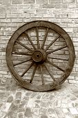 stock photo of wagon wheel  - old wooden ox wagon wheel taken in sepia - JPG