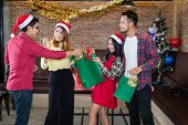 Asian Man And Woman Wear Santa Claus Hat And Holding Green Gift Bag On Hand In Christmas Party. Conc poster