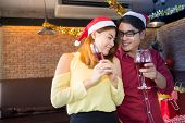 Asian Man And Woman Wear Santa Claus Hat And Holding Champagne Glass On Hand In Christmas Party. Con poster