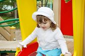 Cute Little Girl Wearing White Blouse And Panama Prepares For Rolling At Slide In Playground