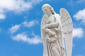 stock photo of sad christmas  - Beautiful white angel with a blue sky background  - JPG