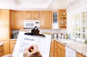 Closeup of a contractors clipboard as he write up an estimate for a kitchen remodel. Shallow depth o