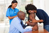 cheerful african mother and her son in doctor's office with doctor and nurse