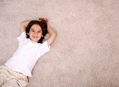 pic of laminate  - Little boy lying on carpet floor at home and smiling - JPG