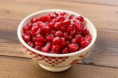 White bowl filled with beautiful ruby red pomegranate seeds
