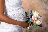 Closeup of a pregnant belly in wedding dress