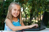 Cute Girl Doing Homework On Laptop Outdoors.