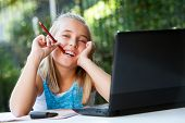 Cute Girl With Pencil In Mouth At Desk.