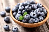 stock photo of dessert plate  - Ripe blueberry in a wooden plate - JPG