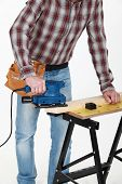 carpenter at work with sander machine