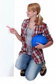 Kneeling tradeswoman pointing sideways