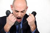 Bald man shouting into two telephones